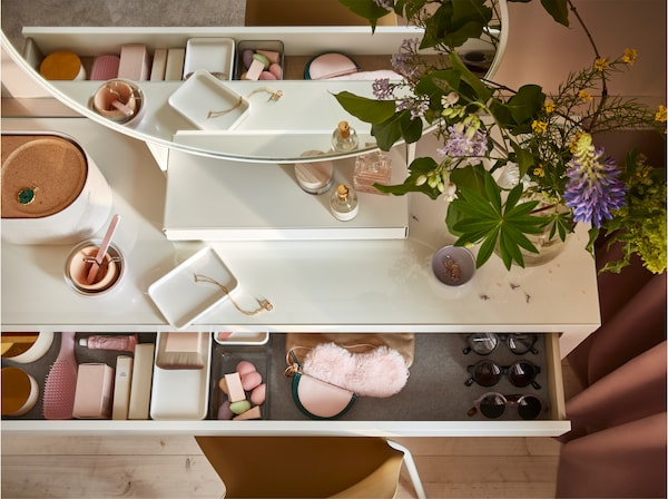 A white dressing table from above, the drawer is open and show makeup sponges, sunglasses and pink accessories stored inside.