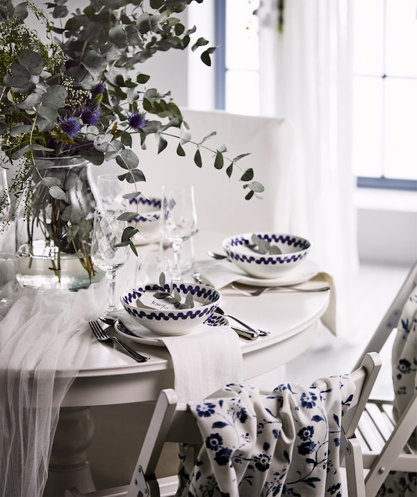 A white, festive round table with a bouquet of wild flowers in a glass vase, and white and blue bowls and plates.