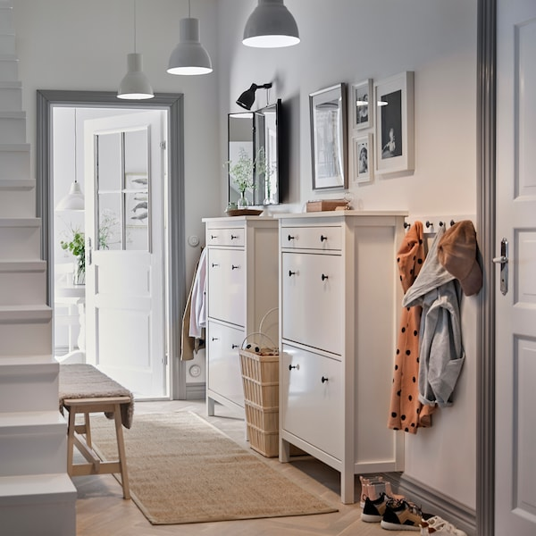 A white hallway with two traditional white HEMNES shoe cabinets side by side and a row of hooks for coats.