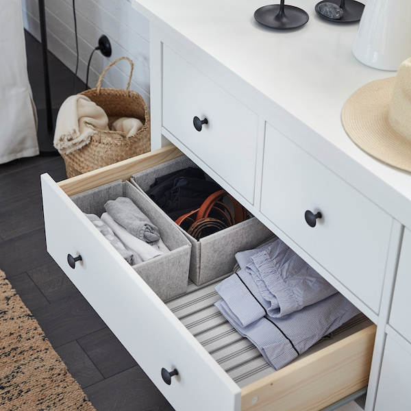 A white HEMNES chest of drawers is open, and KOMPLEMENT light grey boxes inside help organise clothes.