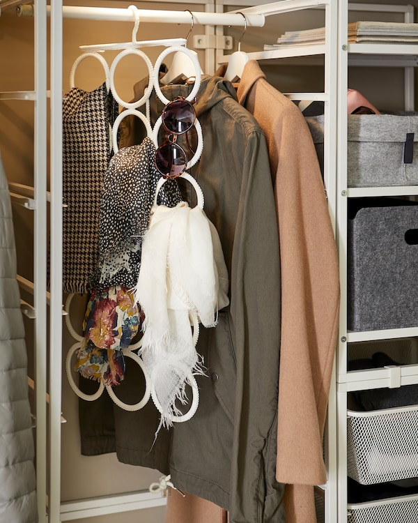 A white IKEA KOMPLEMENT multi-use hanger that organises sunglasses and shawls and is hung on a clothes rail.