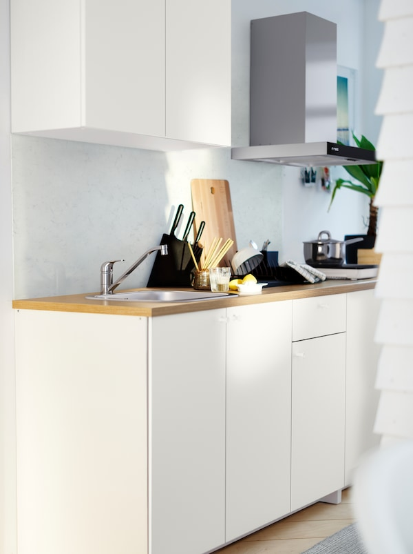 A white KNOXHULT kitchenette with a wooden worktop, potted herbs, pots, knives and various kitchen accessories.