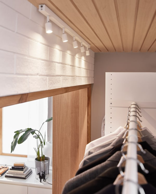 A white LED ceiling track is ceiling-mounted above a wardrobe solution, and the adjustable spotlights illuminate the clothes.