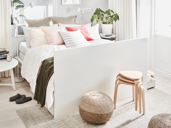 A white MALM double bed, made with many pillows and cushions and having its headboard as foot end, stands in a bright room.
