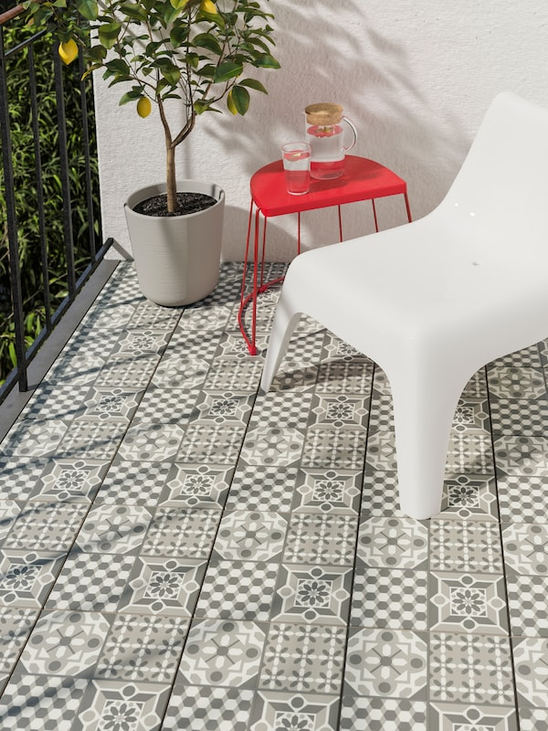 A white plastic outdoor chair with a red outdoor table and a plant in a plant pot on a balcony with designed flooring.