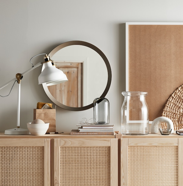 A white RANARP work lamp, books, a round mirror, and two vases on top of a wooden IVAR cabinet with doors.