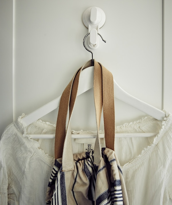A white shirt and bag on a hanger on a white hook.