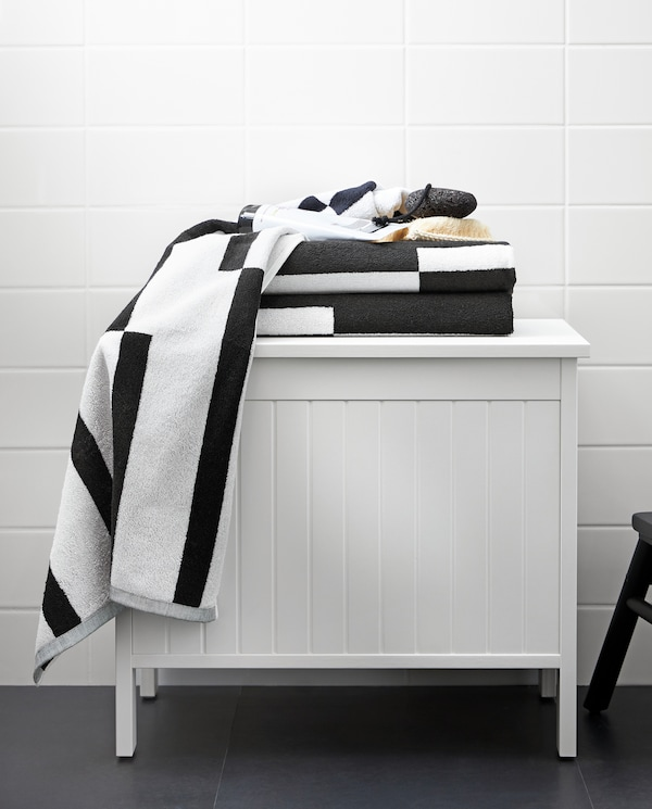 A white SILVERÅN storage bench with towels with a graphic black and white pattern on top of it, standing in a bathroom.