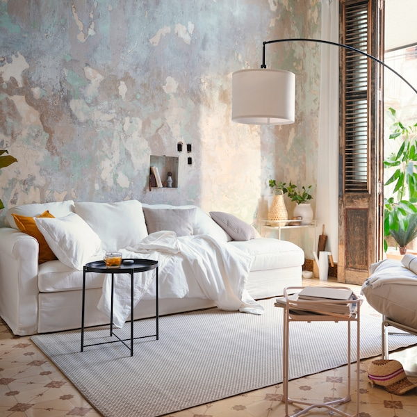 A white sofa placed in a beige-grey, watercolour-style setting with scatter cushions and a black side table.