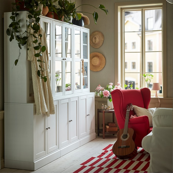 A white storage combination with glass doors in a red and white living room. Green plants are placed on top.