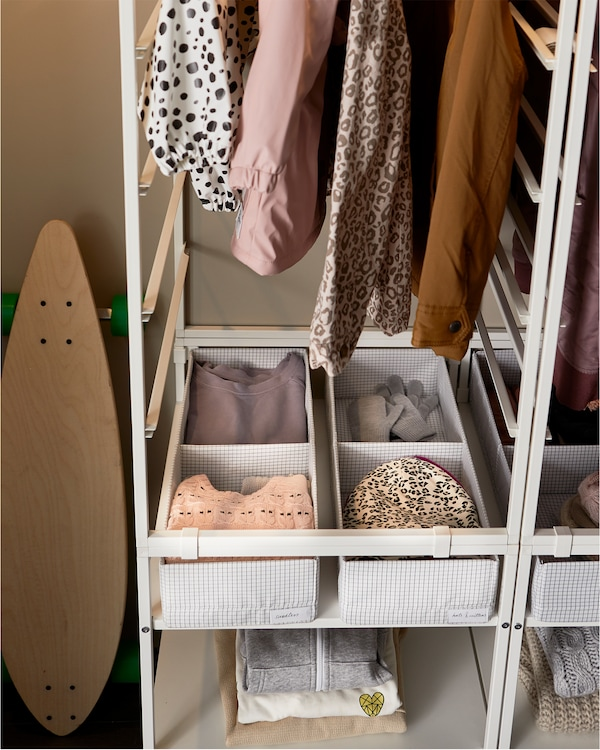 A white storage system, and at the bottom are STUK white and grey boxes with compartments where clothes are organised.