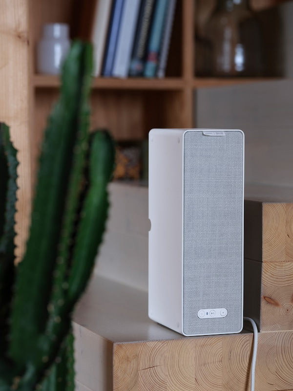 A white SYMFONISK WiFi shelf speaker stands on a wooden set of stairs, with a bookshelf praced behind it.
