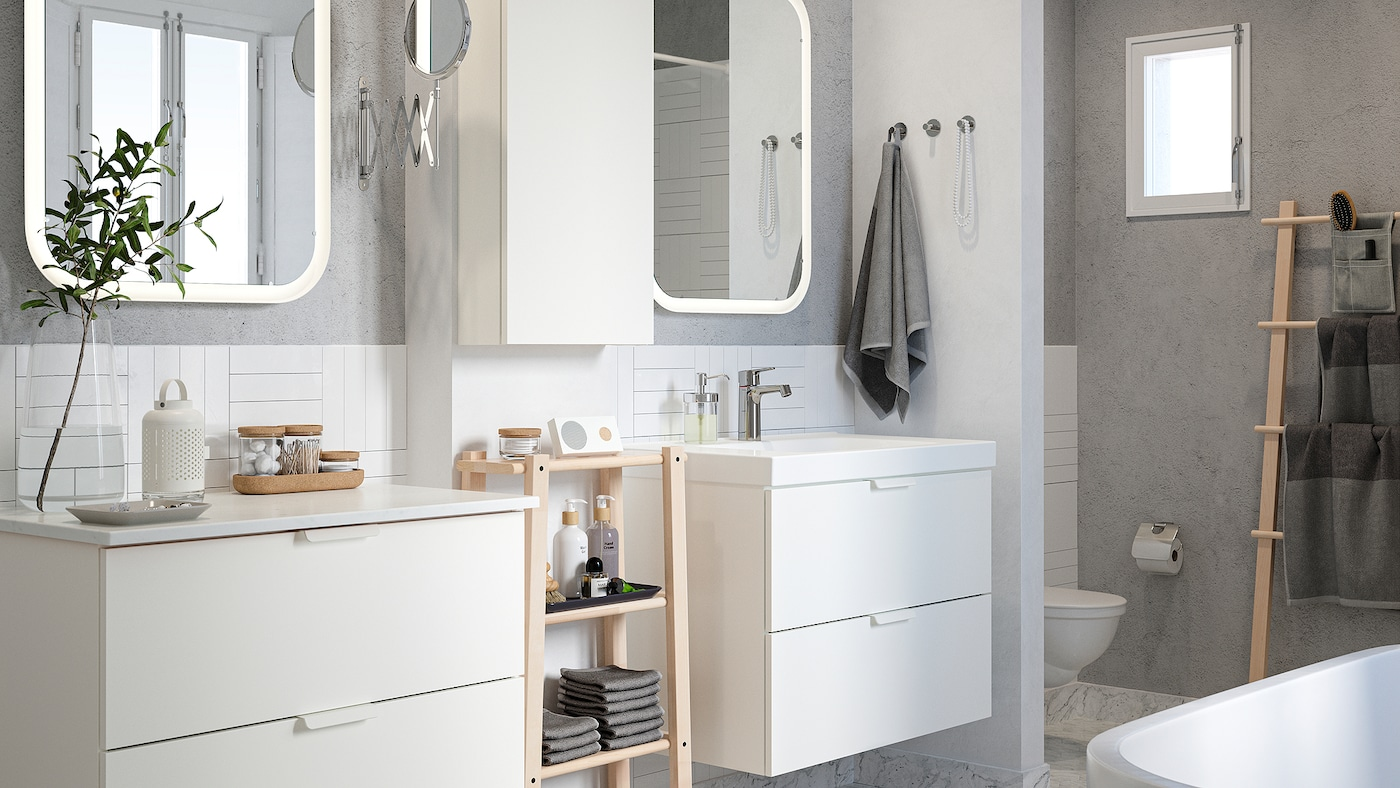 A white-tiled bathroom with grey walls, two wash-stands, mirrors and a shelf in birch with towels and beauty products.