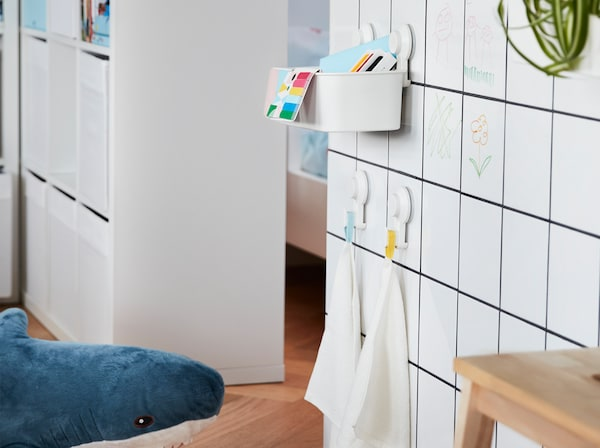 A white tiled wall with TISKEN basket and hooks with suction cups attached to it, they hold children's toys and small towels.