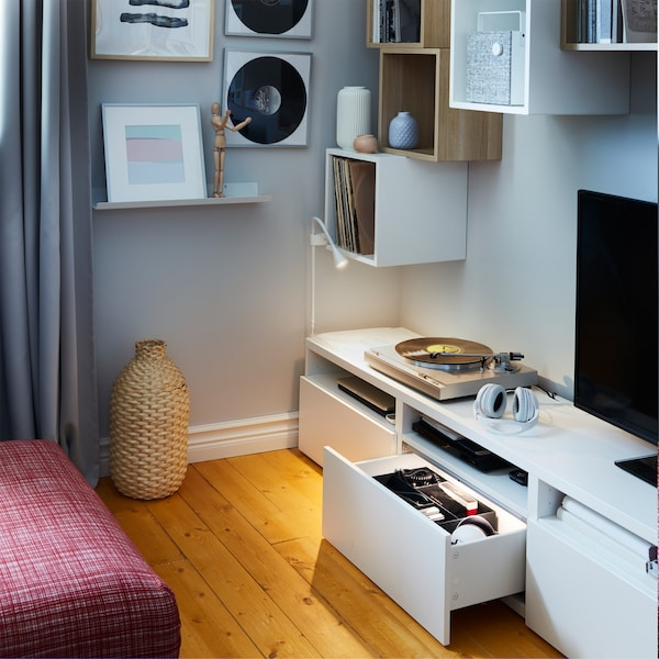 A white TV bench with an open and illuminated drawer, white wall cabinets, a small wall lamp and a decoration vase in bamboo.