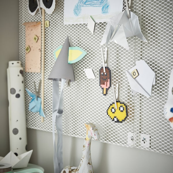A white, wall-mounted SÖDERGARN memo board with magnets and clips, and attached on them are children's crafts and drawings.