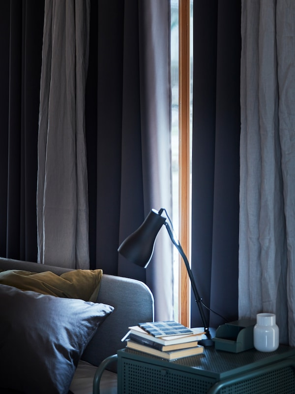 A window in a blue-toned bedroom, with the sun almost entirely hidden by HILLEBORG block-out curtains.