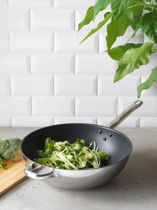 A wok containing fresh green vegetables such as broccoli stands on a grey kitchen worktop.