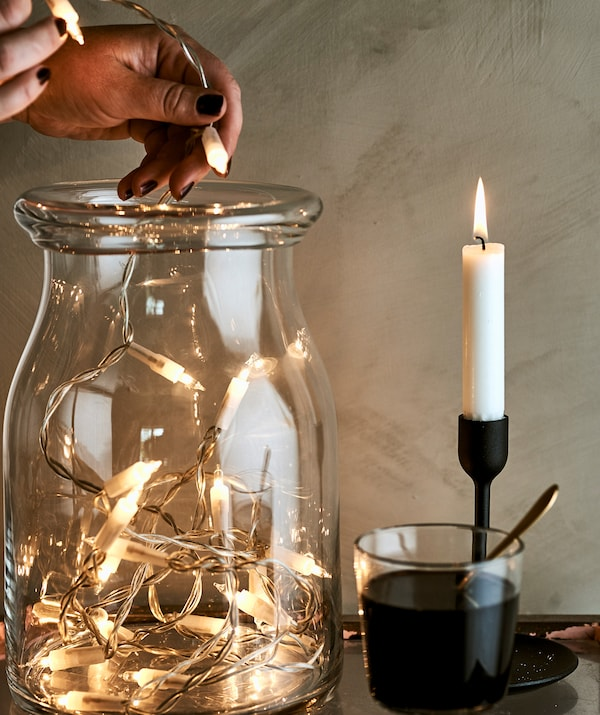 A woman fills a glass jar with decorative fairy lights next to a glass of wine and lit candle in a black candleholder.