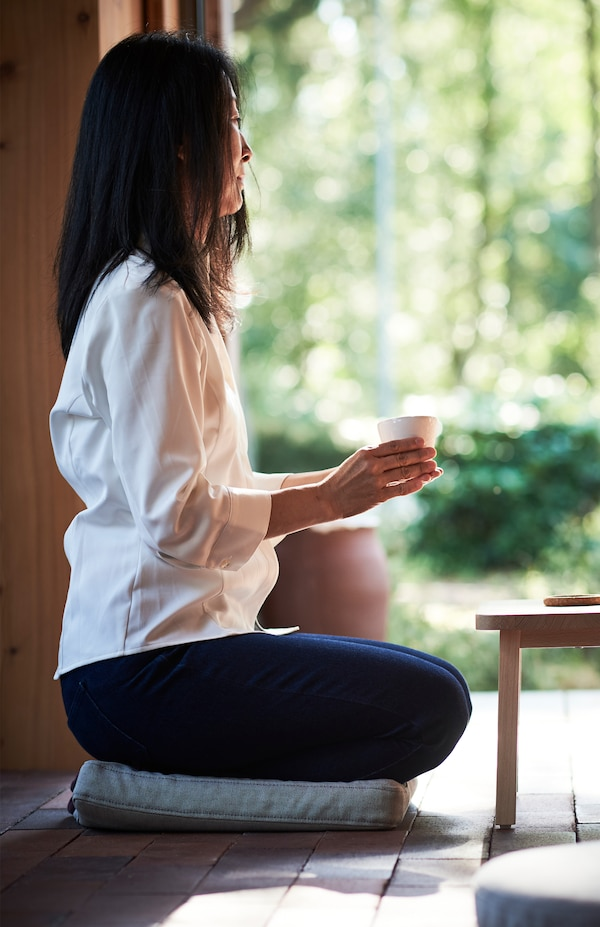 A woman holding a mug in both hands sits on an OMTÄNKSAM chair cushion placed on the floor.