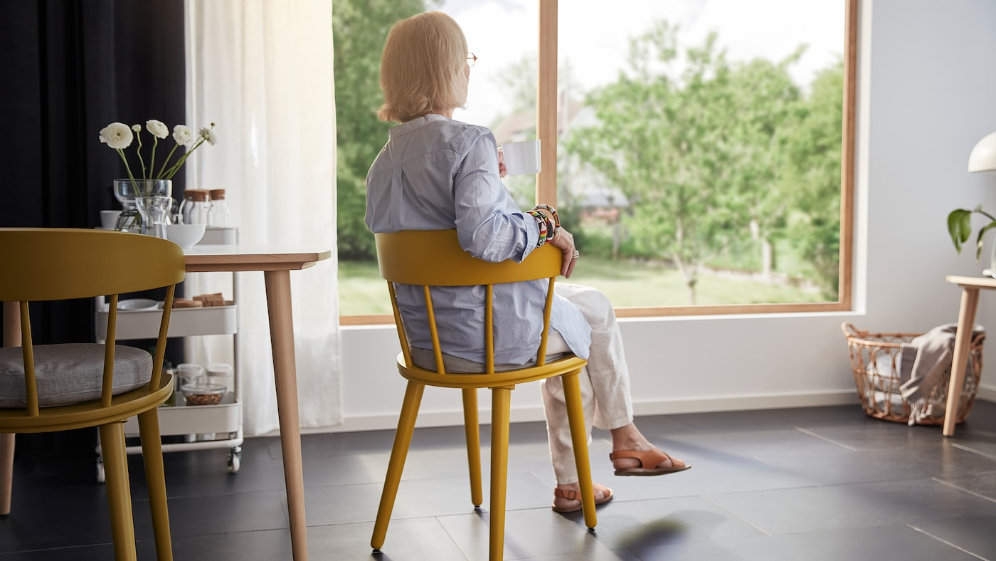 A woman in her 60s sits comfortably in the OMTÄNKSAM chair. She has her back to us and looks out the living room window.