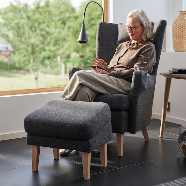 A woman in her 60s sits in an OMTÄNKSAM armchair. The armchair and footstool are placed in front of a large window.