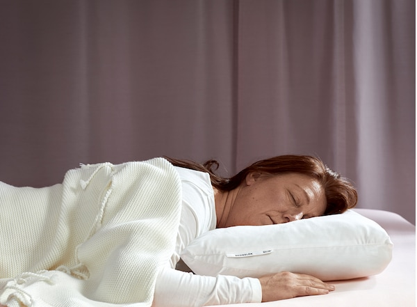 A woman, laying on her stomach, is sleeping deeply on IKEA SKOGSLÖK ergonomic pillow.
