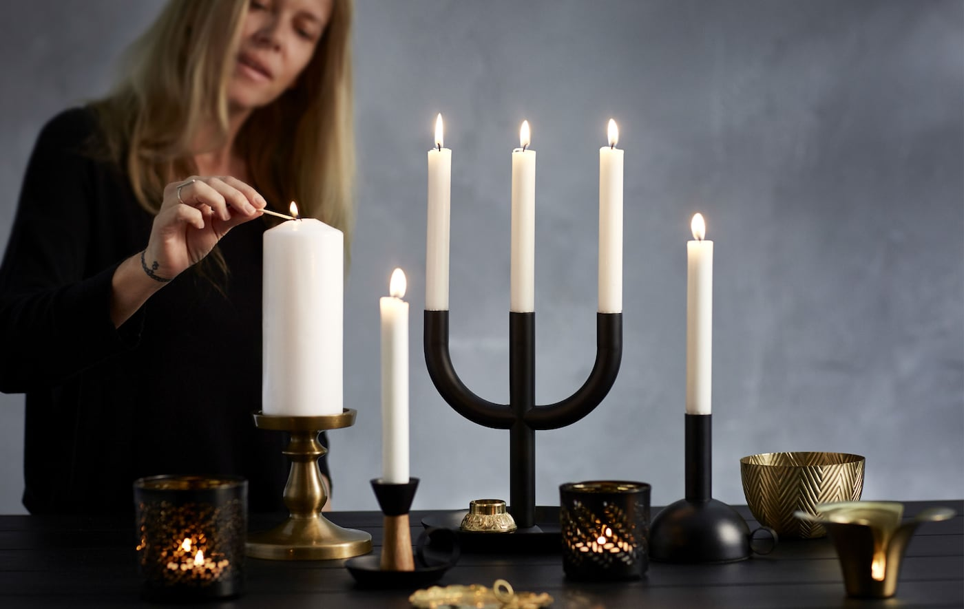 A woman lighting a block candle that is part of a candle display with a mix of candle holders in black and brass.