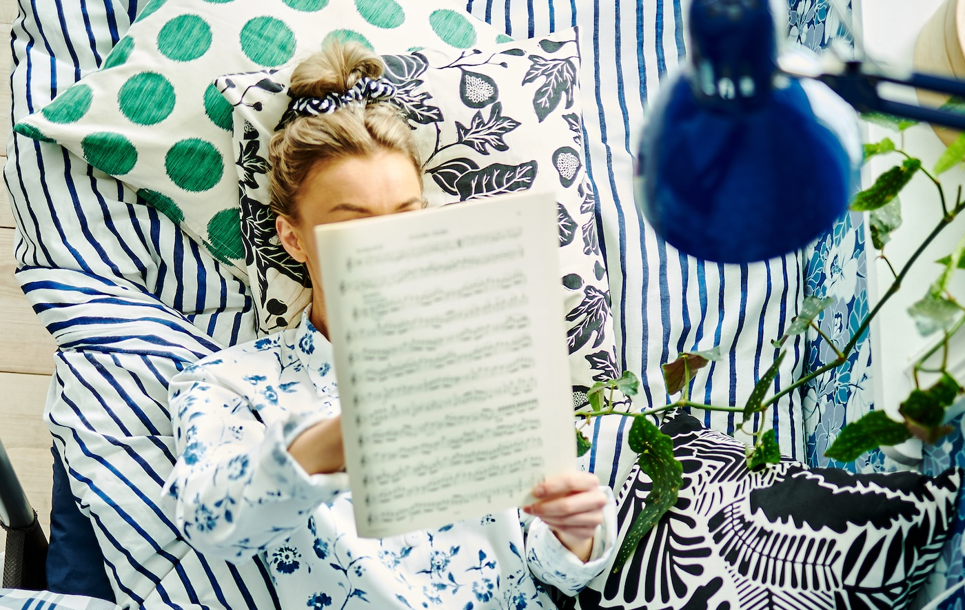 A woman lying in bed with cushions, bed linen and wallpaper with different patterns around her, while reading musical notes.