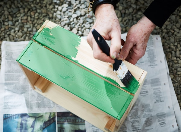 A woman paints a wooden planting box green.
