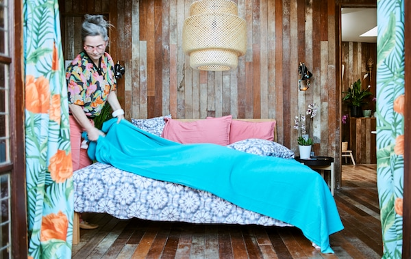 A woman puts a blue throw on a bed with purple tie-dye bedding, in a wood panelled bedroom with large woven ceiling light.