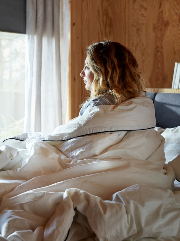 A woman sits upright in bed and looks through a sunny window, while still wrapped in a cream-coloured quilt.