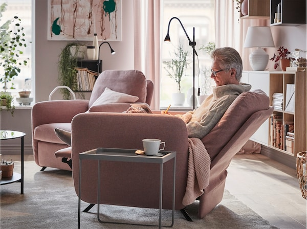 A woman sitting comfortably in EKOLSUND recliner in GUNNARED light brown-pink cover beside a coffee table.