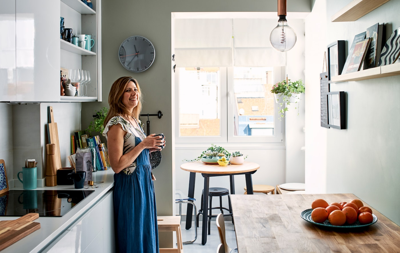 A woman stands in a galley-shaped kitchen with white door fronts, a wooden bar table and small dining area at one end.