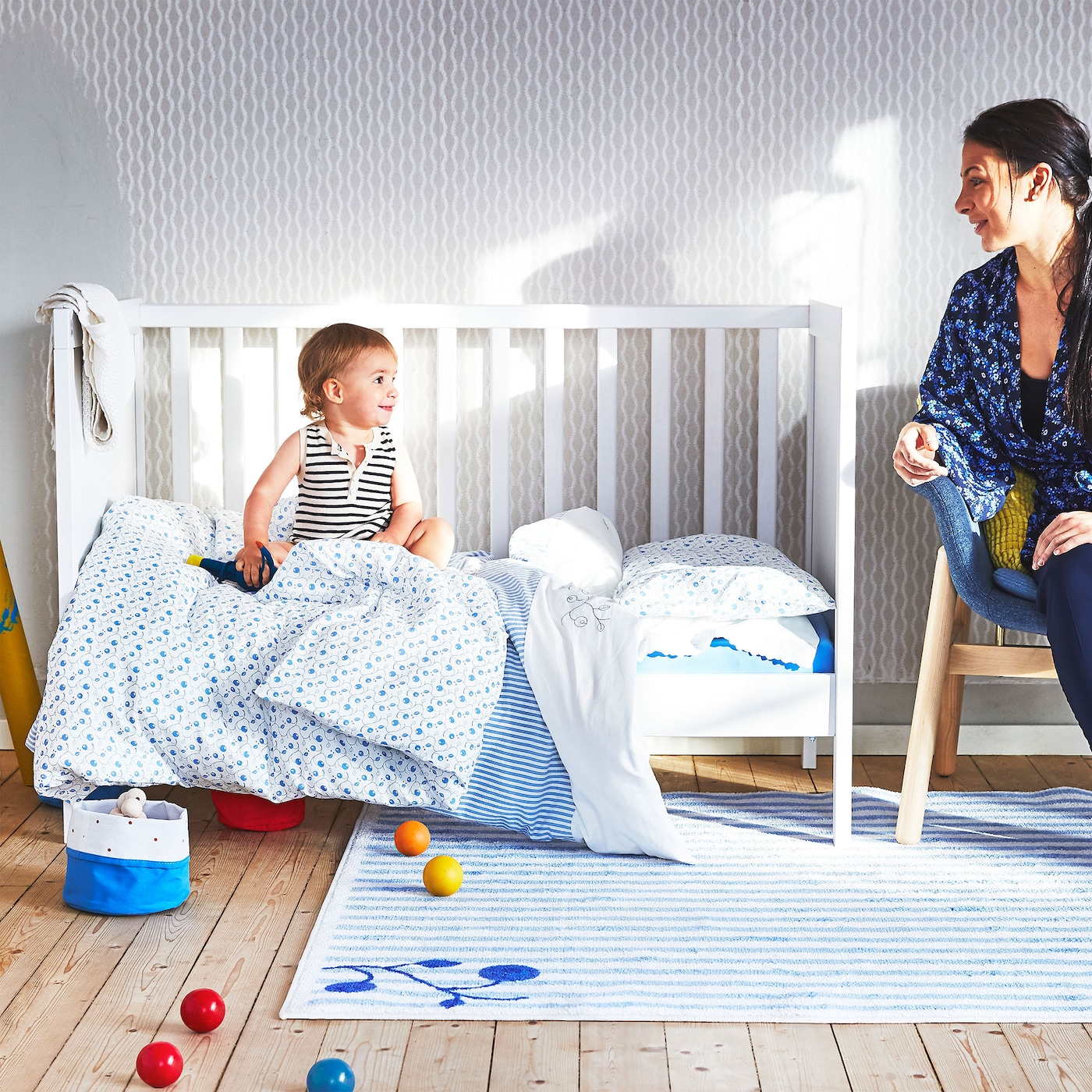 A woman watches a baby on a bed with blue and white GULSPARV baby textiles. A striped GULSPARV rug is in the foreground.