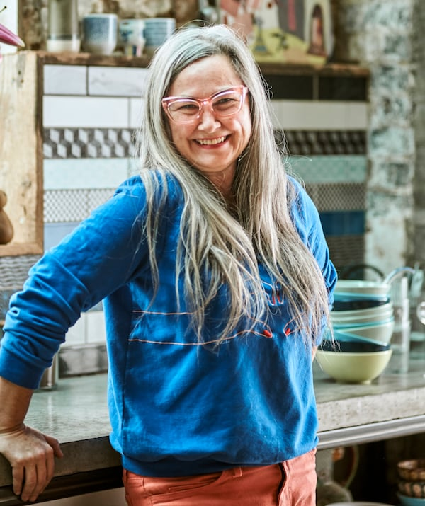 A woman with long grey hair, wearing pink-rimmed glasses, a blue top and red jeans leans against a kitchen worktop smiling.