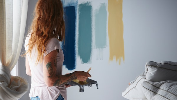 A woman with red hair is standing in a bedroom trying out different paint colours by painting lines on a white wall.