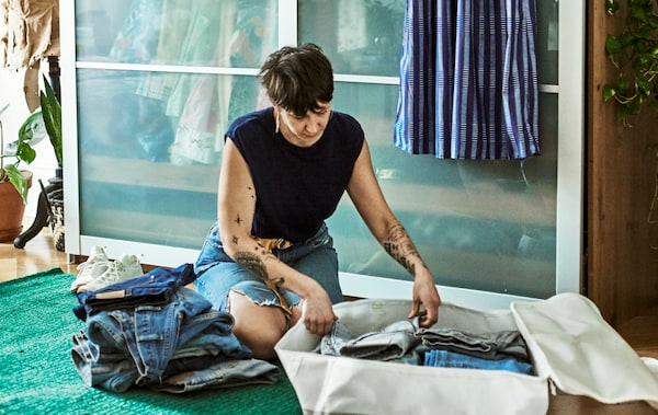 A woman with tattooed arms sits in a bedroom on a green rug sorting a pile of blue jeans into a big cream fabric storage bag.