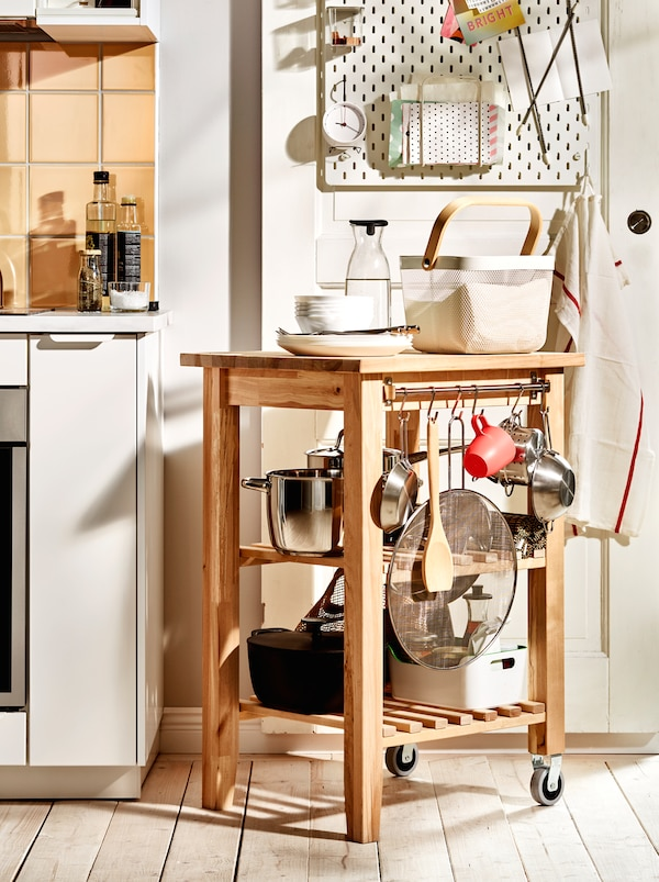 A wooden BEKVÄM trolley with pots, pans and other kitchen accessories placed as a continuation of the worktop surface.