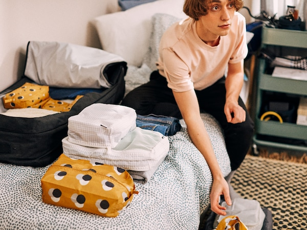 A young student sits on his bed surrounded by the things he's packing for college, neatly organised in RENSARE bags.