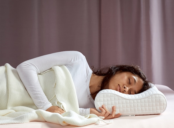 A young woman, laying on her side, is sleeping deeply on IKEA ROSENSKÄRM ergonomic pillow.
