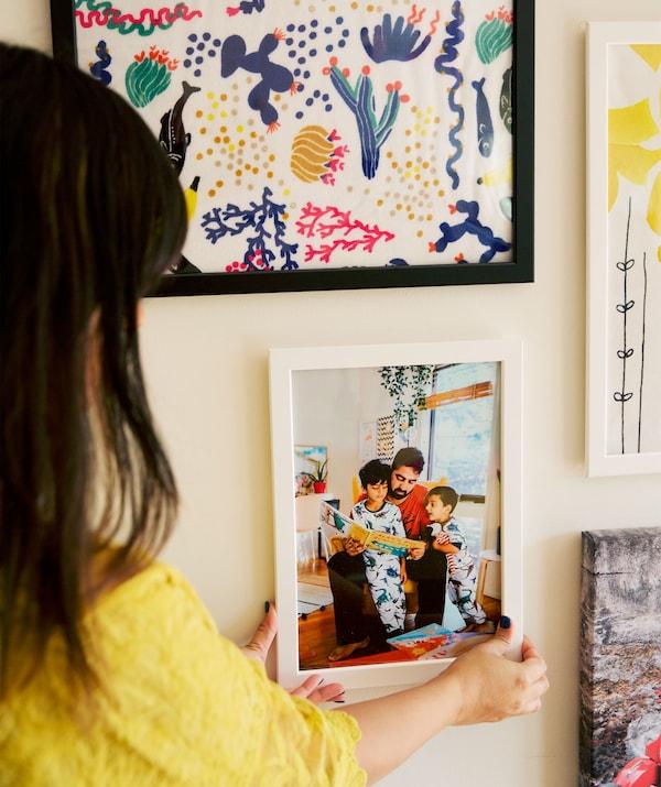 Abeer将一张全家福挂在了图片墙上。