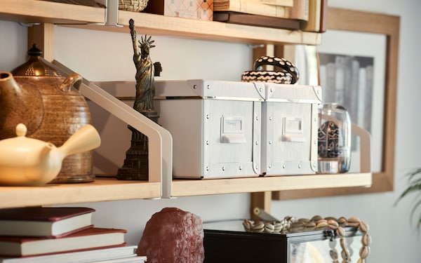 Add a few IKEA FJÄLLA boxes to your shelving to keep smaller items, paper, and more tidy and dust-free.