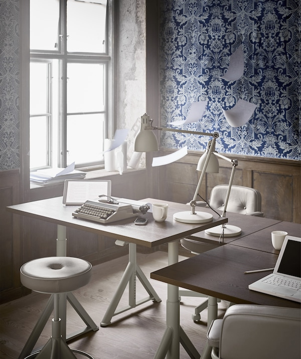 An adjustable desk and swivel chair next to a window in an office with blue patterned wallpaper.