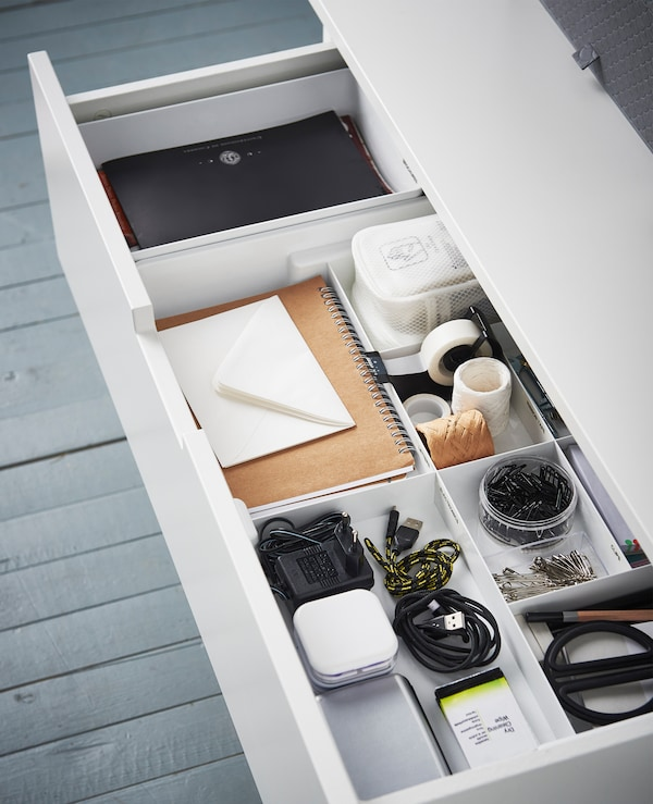 An aerial view of a drawer and an insert with compartments for organised scissors, tape, cords, tape, etc.