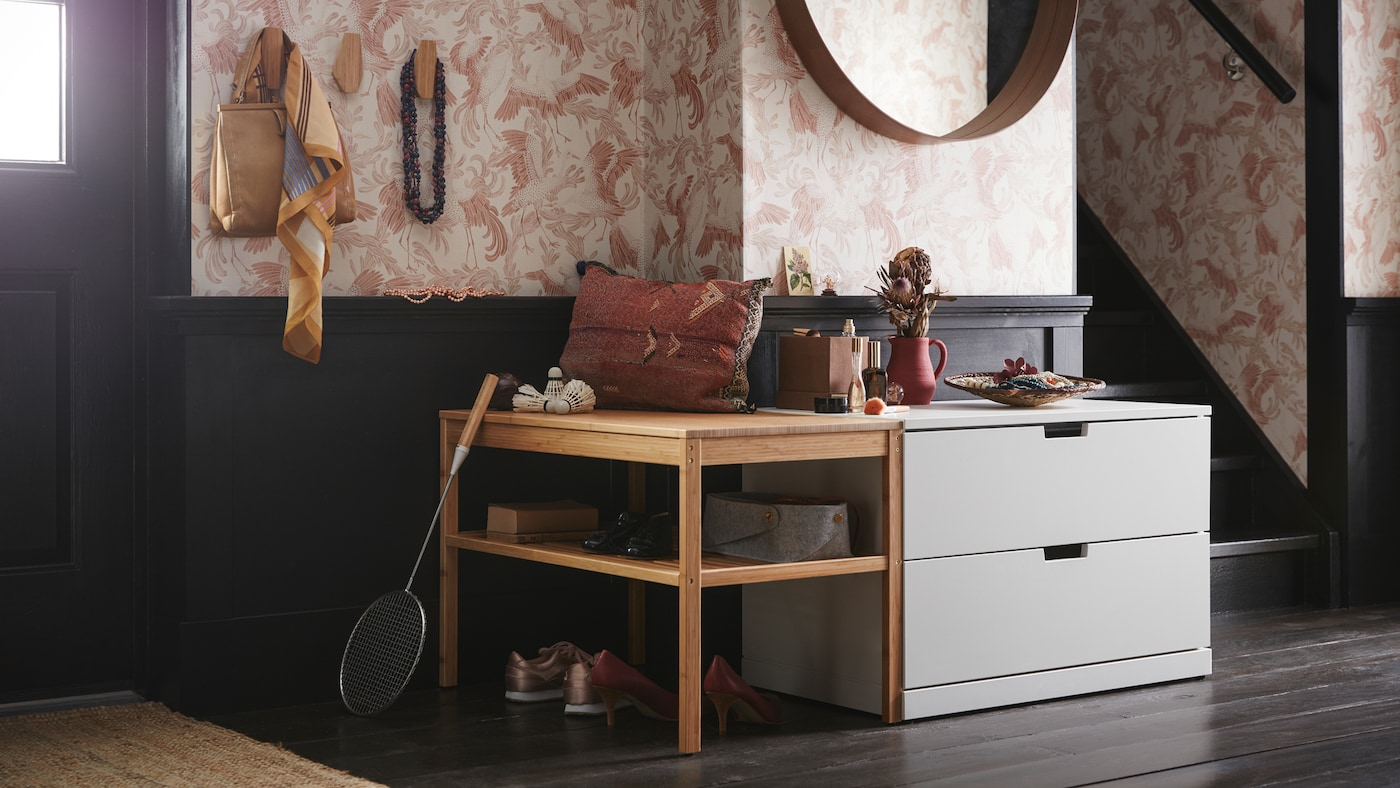 An entrance with a light grey NORDLI chest of two drawers under a round mirror and beside a wooden bench with open shelves.