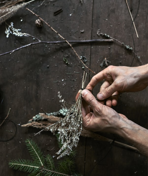 An image of hands tying a sprig of foliage with black sewing thread.