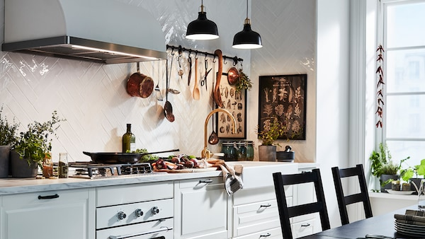 An off-white kitchen with traditional BODBYN doors and drawer fronts is illuminated by two black pendant lamps.