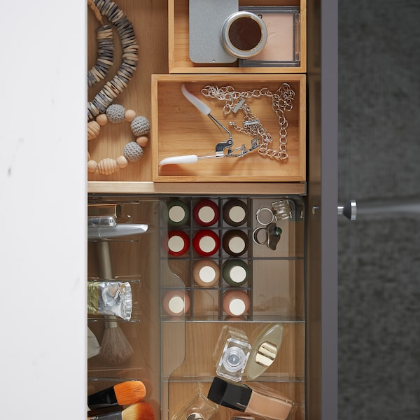 An open bathroom drawer holding an organiser in transparent plastic with make-up, and DRAGAN bamboo boxes with accessories.