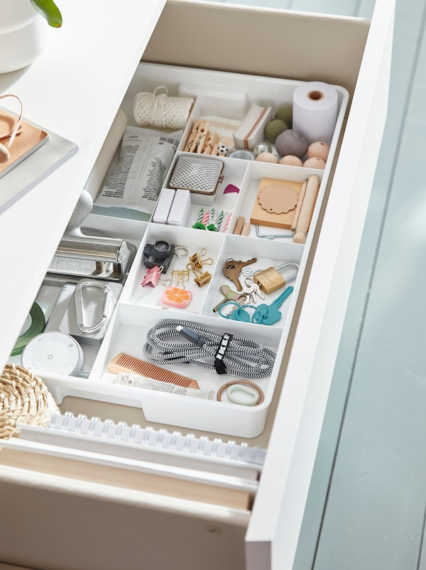 An open drawer with white KUGGIS inserts with eight compartments inside filled with keys, clips, string and office supplies.